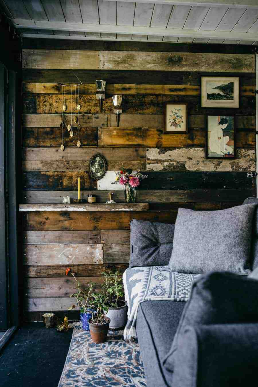 love the reclaimed wood panelling and grey scandi influenced sofa and cushions inside Jeska Hearne's garden office workshop/ tea shed