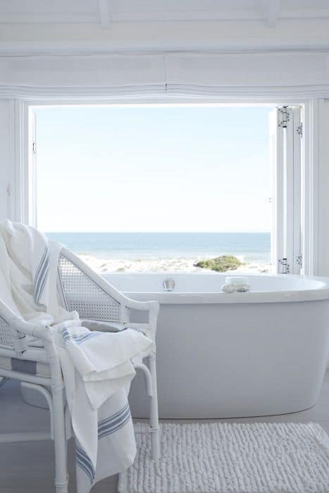 love this dreamy white coastal bathroom with views to the sea