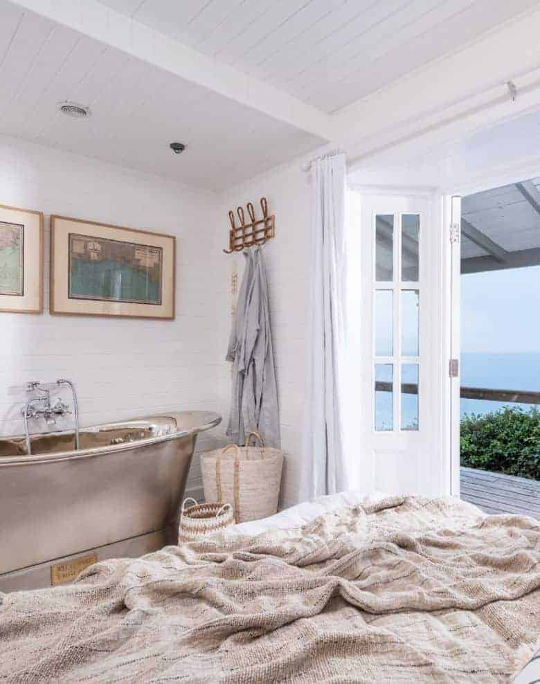 coastal interiors bedroom idea roll top metal bath with french doors to terrace and painted white tongue and groove walls