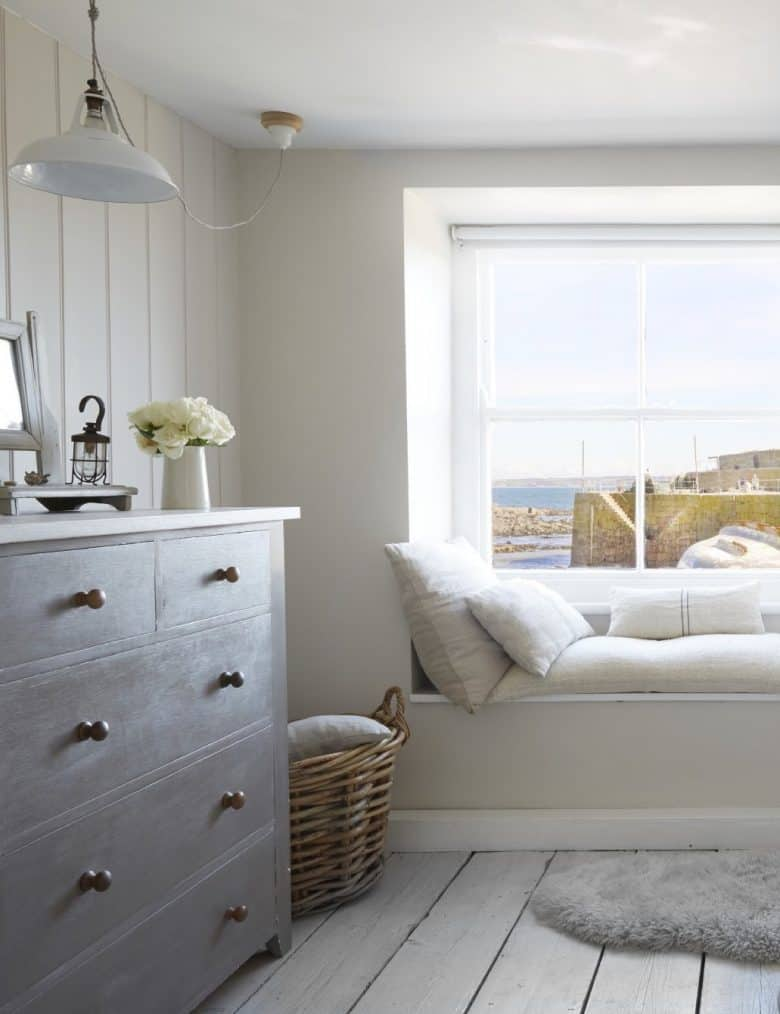 love this coastal interiors bedroom idea for making a simple window seat with grainsack linen cushions and painted whitewashed floorboards and vintage furniture with tongue and groove panelling on the walls