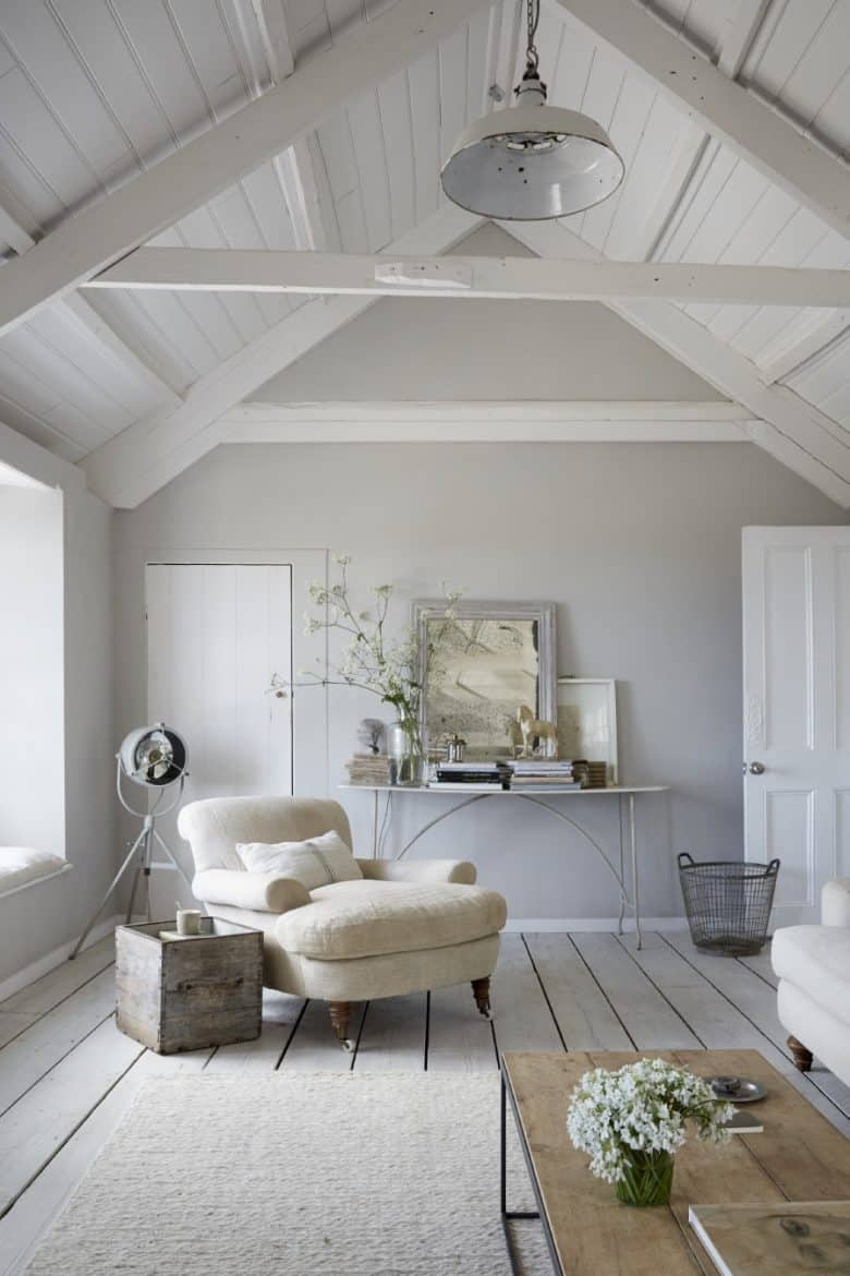 coastal interior idea living room in soft greys whites, painted white washed floorboards, vintage accessories, linen covered arm chair and seaside finds - its the Oyster Catcher in Mousehole, Cornwall, and bookable through Unique Home Stays - all the info you need to book is in the blog post - as are lots of other inspiring interiors ideas #coastal #interiors #seaside #decor