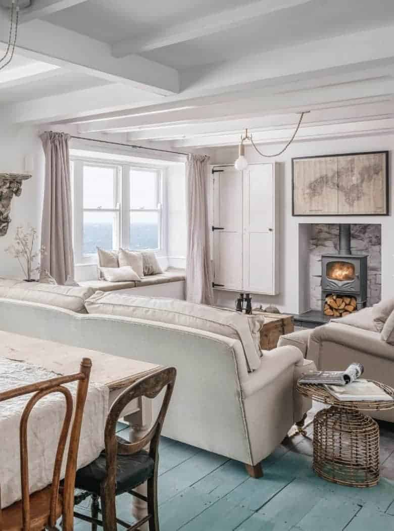coastal interiors living room idea with woodburner, window seat, floorboards, rustic wood, vintage map and soft pink linen curtains with natural linen cushions and sofas #coastal #interiors #livingroom #woodburner #windowseat #seaview