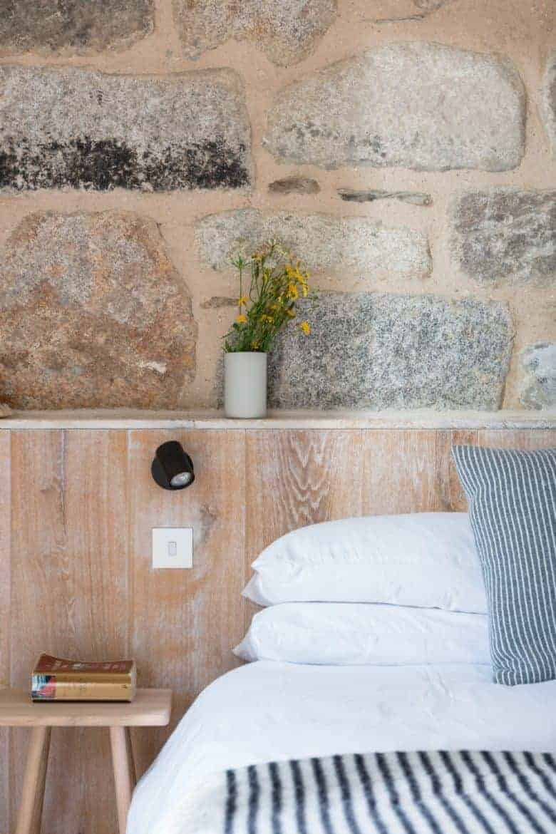 love this coastal interiors bedroom idea from The Meadows in Cornwall (bookable through Unique Home Stays - all the info is in the blog post) - love the combination of natural old stone, whitewashed wood to create a simple bed headboard and crisp white bed linen with blue marine stripe throw #coastal #interiors #whitewash #headboard #stone