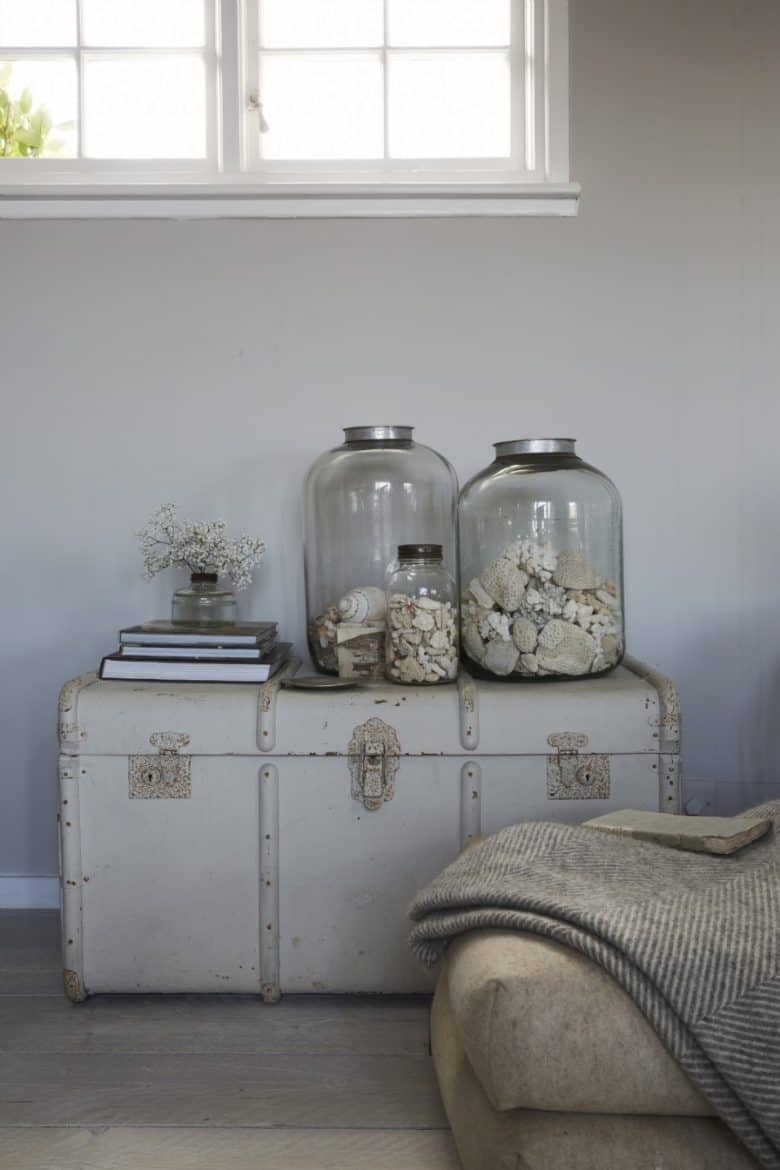 coastal interiors jars of shells on painted old vintage antique trunk as side table