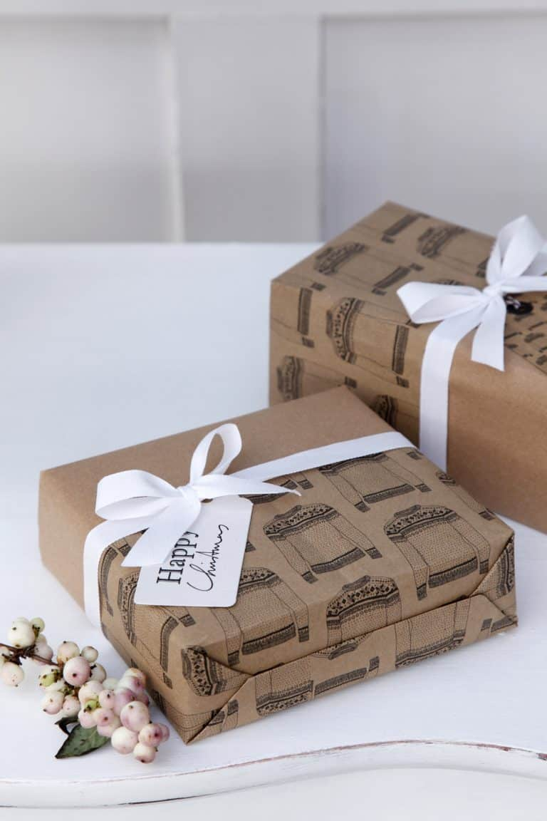 love this kraft paper with white ribbon and berries christmas gift wrapping idea. Love how the plain brown paper is contrasted with christmas jumper wrap by katie leamon. Click through for more festive wrap ideas you'll love