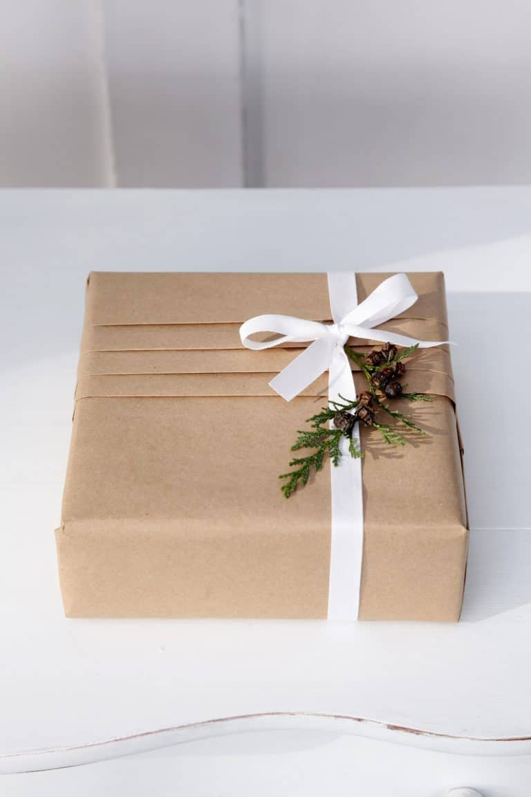 love this pleated brown kraft paper with white ribbon and fresh green fir leaves christmas gift wrap idea by jane means. click through for more festive gift wrap ideas you'l love