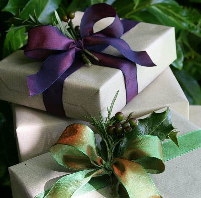 love this kraft paper with rich purple and seasonal green ribbons and foliage by jane means. click through for more creative and simple to do festive wrapping ideas