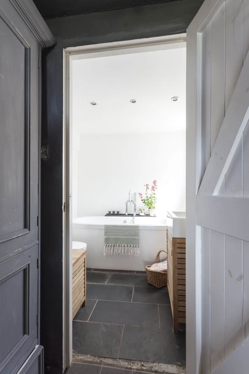 love this white and grey coastal bathroom with farrow and ball grey walls, slate floor and simple white bath accessorised with baskets