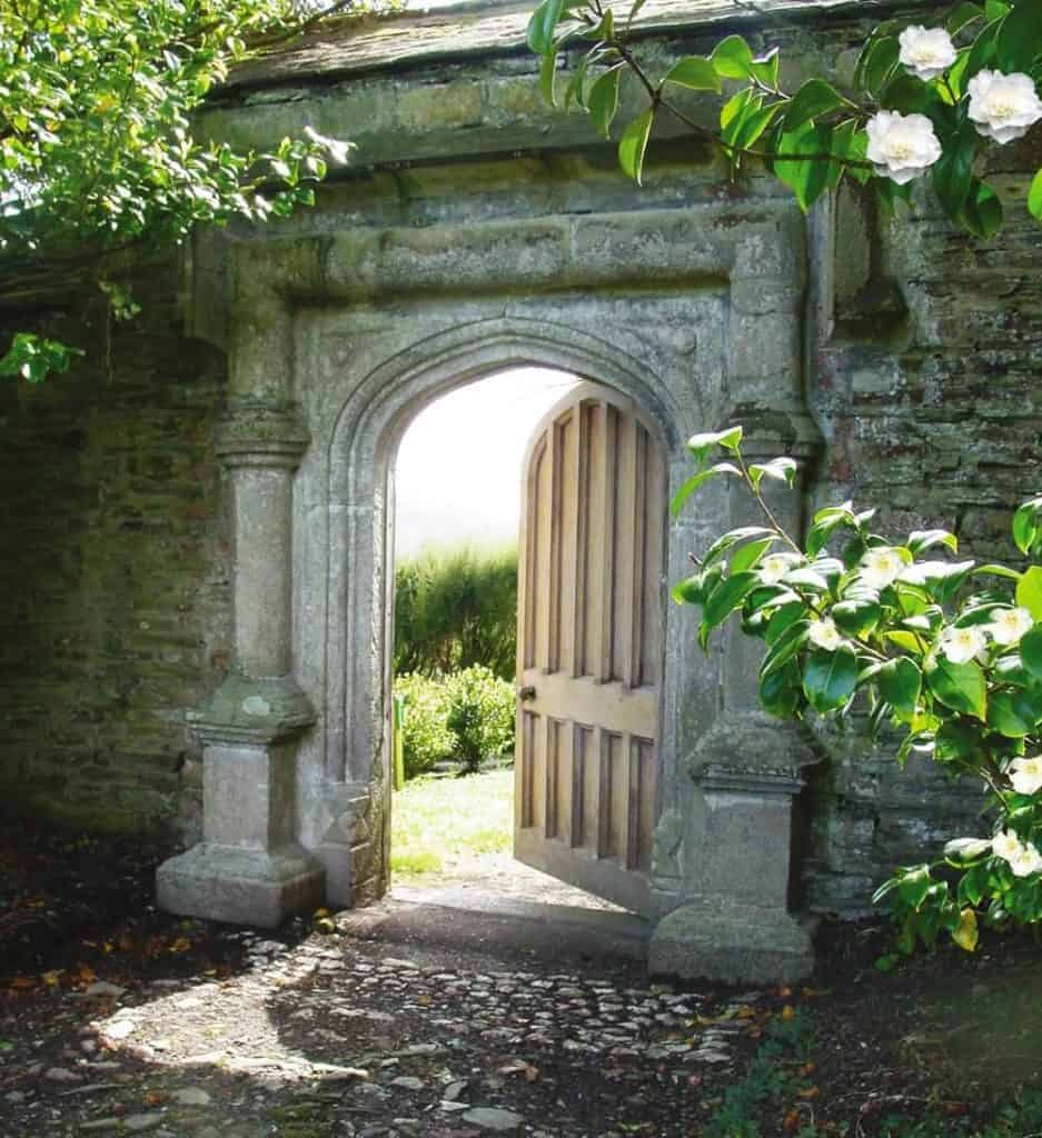 beautiful old stone archway with wooden garden door at Tregothnan english tea estate cornwall