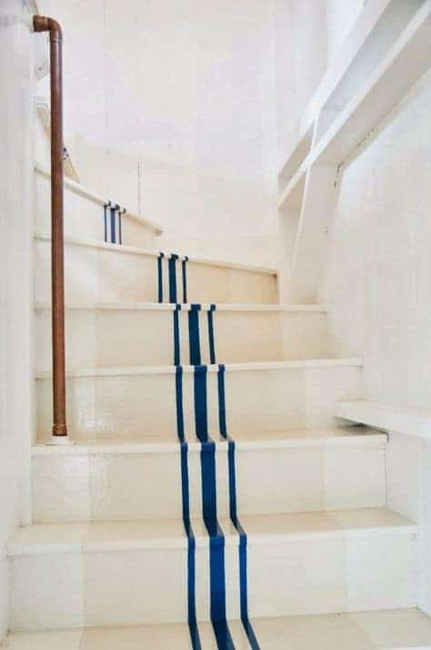 white painted stair case with blue stripes. Coastal seaside hallway staircase idea. Click through for more coastal decorating ideas you'l love