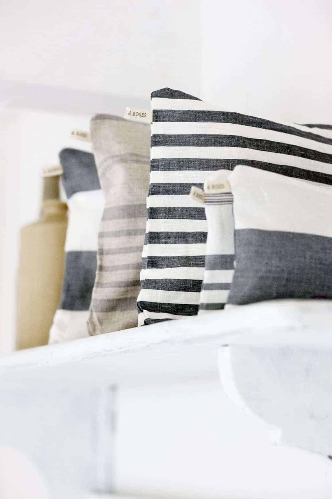 love these striped linen cushions by cabbages & roses in charcoal greys, pale greys and dark blues and white. Click through for more details and for other coastal and seaside interiors ideas you'll love
