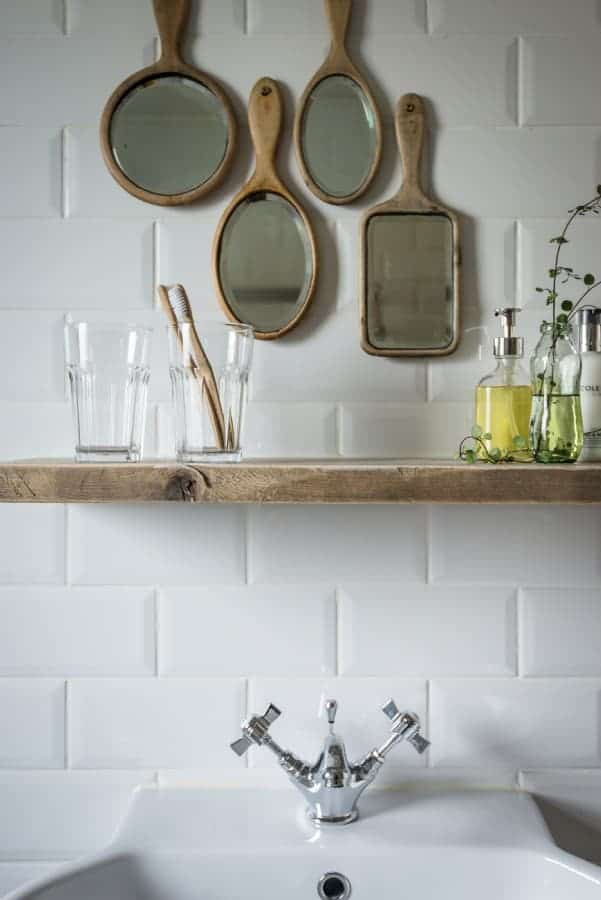 coastal bathroom with white metro tiles, reclaimed rustic wood shelf and vintage wooden hand mirrors to add a quirky individual touch. Click through for more ideas you'll love