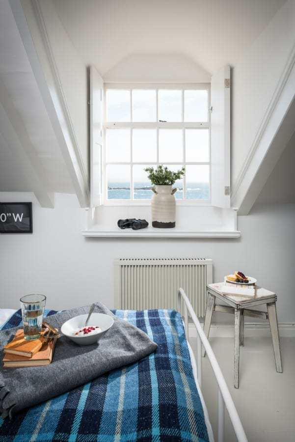 love this fresh blue and white coastal bedroom with white metal bed, check blue and greys wool throw blankets, vintage painted stool and gorgeous white shutters at the window with sea view