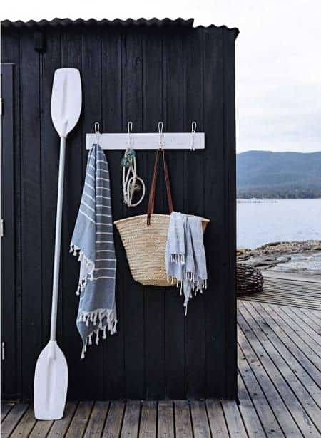 love this outdoor lakeside shower with oars and rustic coat hooks for baskets and striped hammam towels