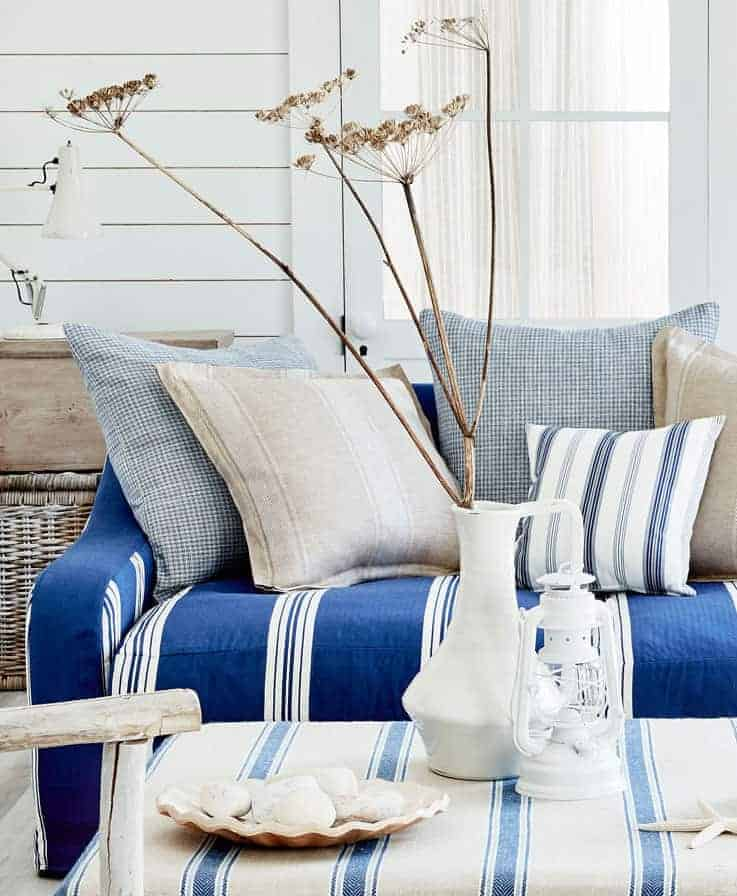 love this coastal living room with sofa and cushions in seaside inspired linens by Ian Mankin. Click through for more details and for other coastal and seaside interiors ideas you'll love