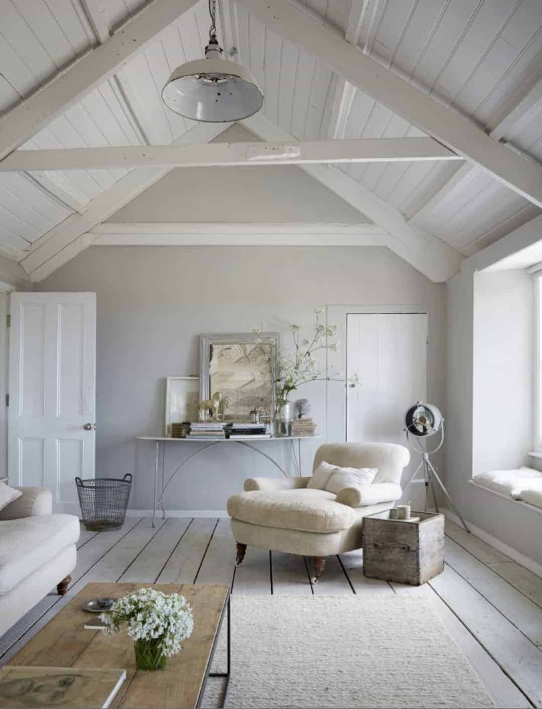 love this seaside coastal vintage loft living room with whitewashed floorbards, vaulted white ceiling and soft grey walls