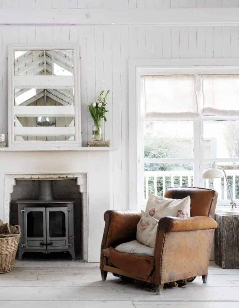 love this simple seaside interior living room with white tongue and groove walls, old leather armchair, woodburner and rustic textures
