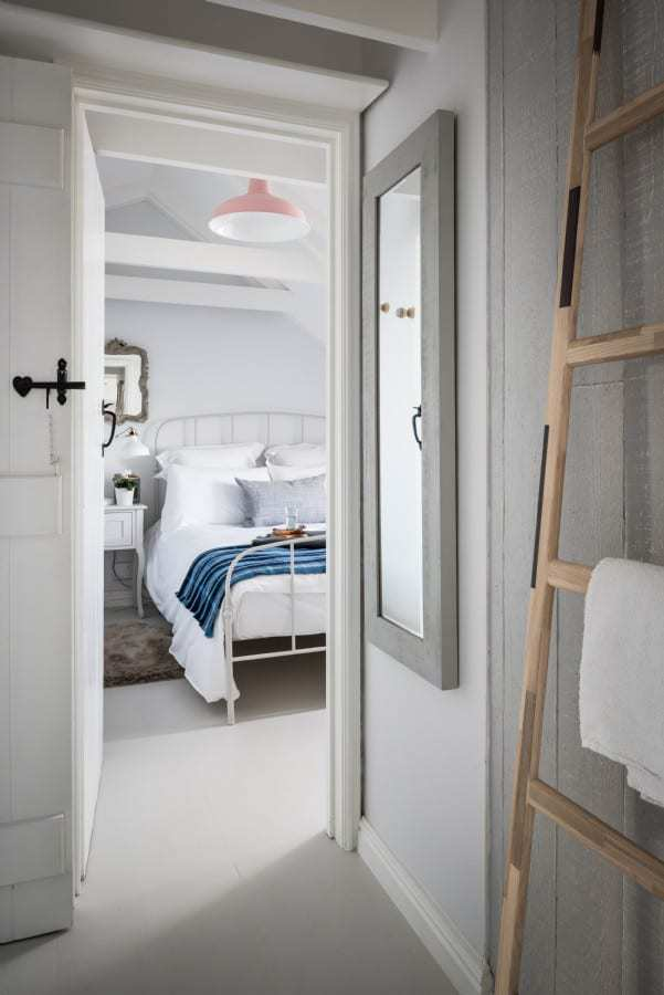 love this seaside interiors bedroom with crisp white linen, blue check blanket, blue linen cushion, vintage french and simple rustic furniture and towel ladder. Click through for more ideas you'll love