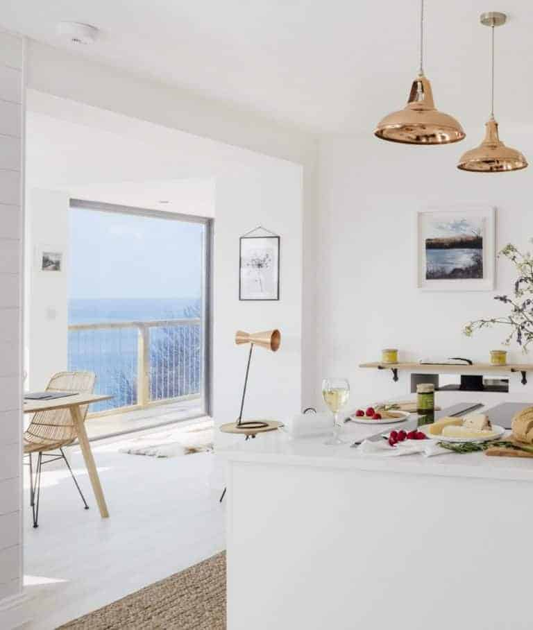 love these sleek sliding doors with white painted wooden floor boards, white kitchen unit with natural jute rug and scandi blonde wood dining table and rattan chairs with views to wooden deck balcony terrace and pair of copper pendant lights. Click through for more seaside interiors ideas you'll love