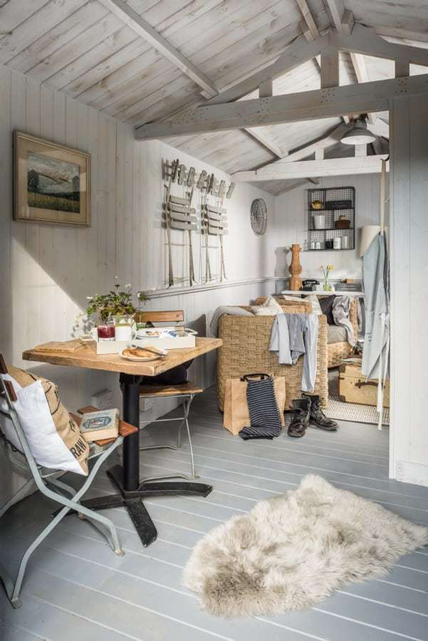 love this coastal painted and white washed wood summer house with white painted floorboards, whitewashed tonge and groove wood panelled walls and beams in soft greys and whites, vintage french metal chairs, wicker and baskets, galvanised wire shelf cube storage and simple reclaimed wooden table