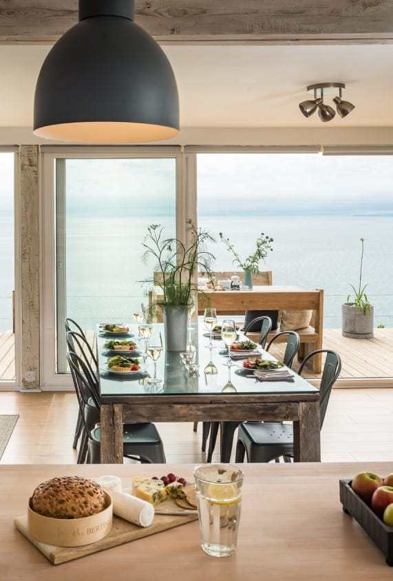 love this simple modern rustic industrial wood and metal dining table with seaview deck balcony terrace and wild flowers in galvanised metal jugs and planters