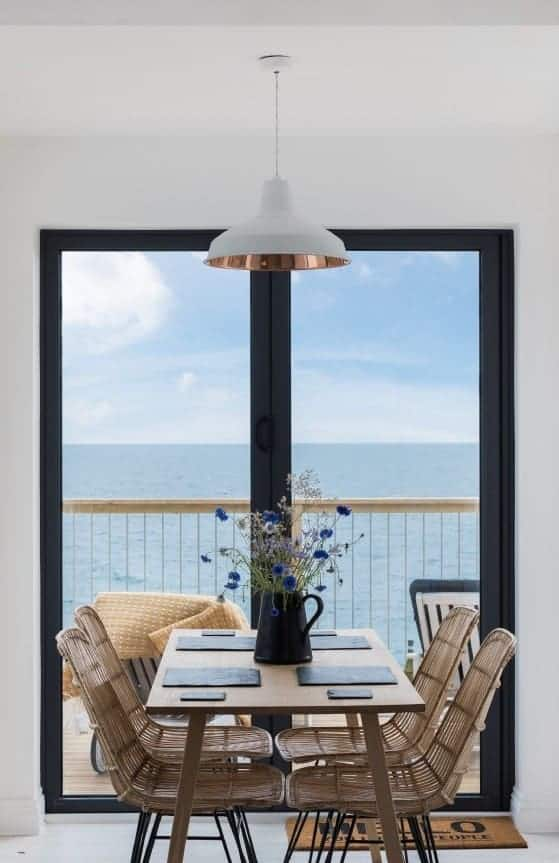 love how these dark grey metal french doors frame the sea view out to the balcony terrace deck area with simple scandi wooden dining table and rattan chairs with rustic vintage metal jug of wild flowers and cornflowers. Love the symmetry and simple scandi modern rustic styling. Click through for more coastal dining room ideas you'll love