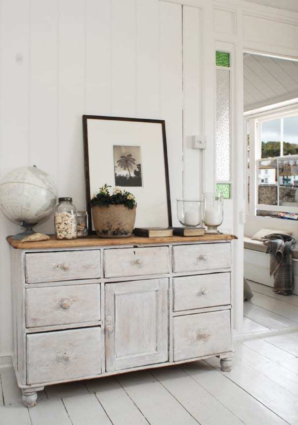 love this seaside coastal living room in Cornwall with painted white floorboards, distressed painted white washed vintage drawers and furniture, window seat with linen cusion and simple shells in vintage jars with storm lanterns and candles... click through for more coastal living room ideas you'll love