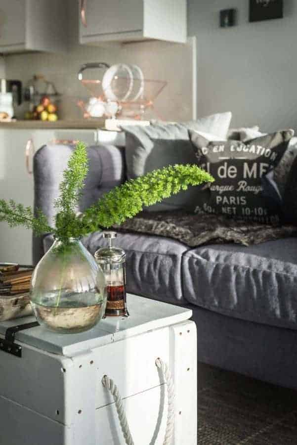 love this seaside interiors living room sofa kitchen with grey linen sofa, fresh green flowers painted white wooden crate as coffee table and seaside cushions