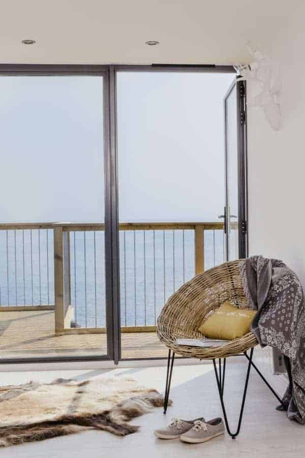 love this midcentury scandi modern and minimalist seaside bedroom with fur rug, scandi wicker bucket chair, sleek metal bifold french doors and wooden decking balcony terrace. Click through for more seaside interiors ideas you'll love