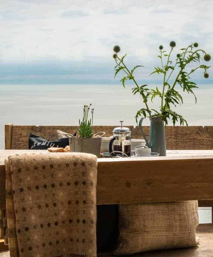 love this seaside interiors outside terrace with rustic wood, welsh wool blanket and simple wild flowers