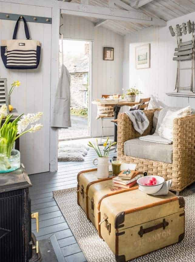 love this coastal painted and white washed wood summer house with white painted floorboards, whitewashed tonge and groove wood panelled walls and beams in soft greys and whites, vintage french metal chairs, wicker and baskets, galvanised wire shelf cube storage and vintage leather trunk as coffee table. Click through for more coastal interiors ideas you'll love
