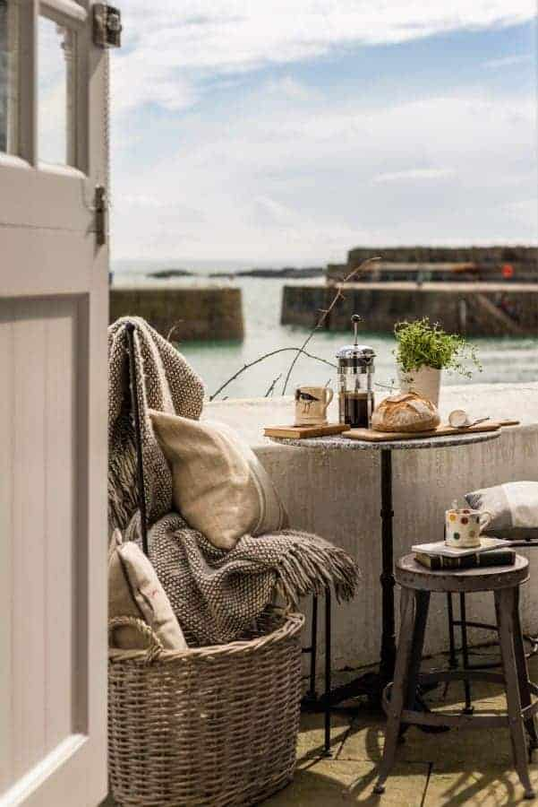 love this rustic seaside interiors terrace morning coffee by sea with wool throw, rustic vintage wooden stool, basket, farrow and ball door and linen cushions. Click through for more coastal and seaside style ideas you'll love