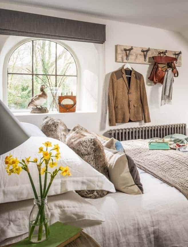 love this vintage modern rustic coastal bedroom with white linen bedding, jam jar flowers narcissi, fur and linen and velvet cushions and reclaimed wooden hanging hooks. Click through for more ideas you'll love