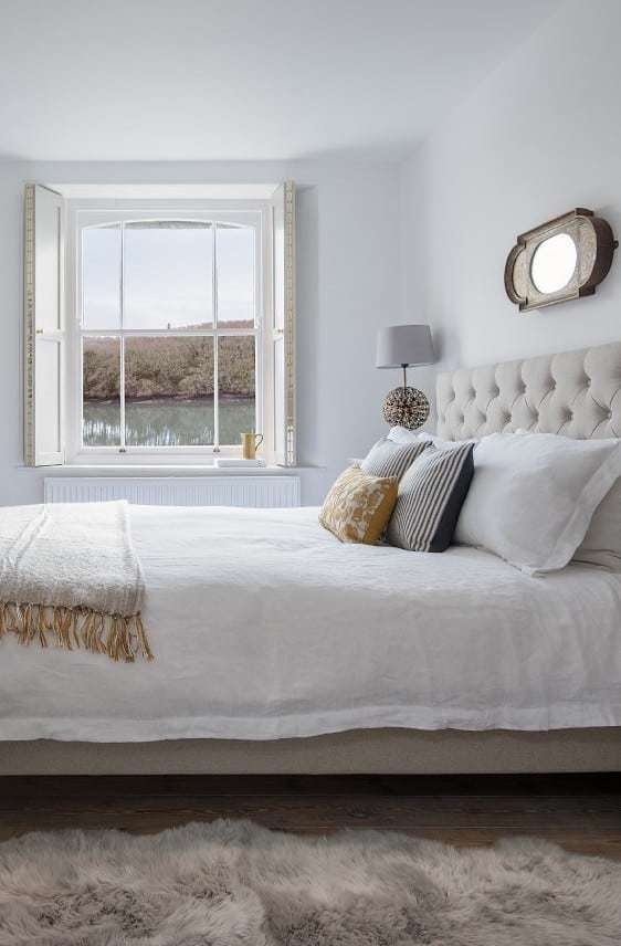 love this simple white coastal bedroom with crisp white linen sheets with pale natural velvet headboard, soft fur rug, natural wood floorboards and gorgeous painted shutters. Click through for more ideas you'll love