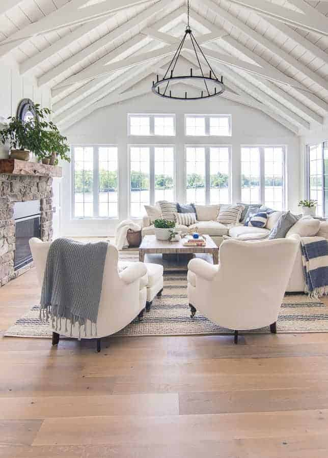 love this blue and white and natural wood living coastal living room with pale wood floorboards, white linen covered chairs and sofa with fresh blue and white linen cushions and soft blue and grey knit throws. click through for more coastal and seaside interiors ideas you'll love