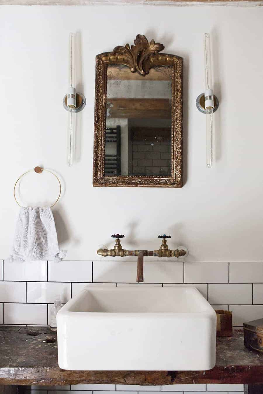 love this modern rustic bathroom by Joraima Tromp of Bricks Studio Amsterdam, with white square sink, old brass taps, vintage gilt mirror and rustic wood top with white metro tiles. Click through for more modern rustic country interiors you'll love