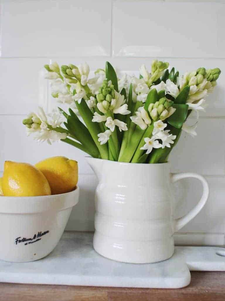 love this modern rustic kitchen look with white creamware jug and white hyacinths