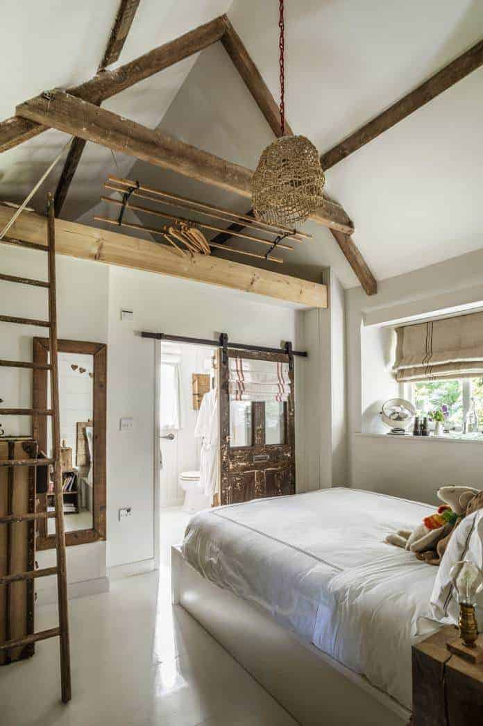 love this white modern rustic country farmhouse bedroom with rustic wooden beams, reclaimed wooden ladder and sliding bathroom door and simple white painted floor. Click through for more modern rustic farmhouse interiors ideas you'll love
