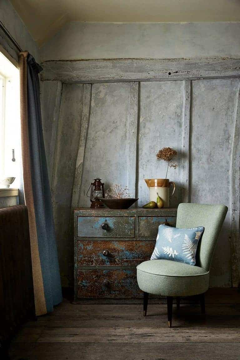 love this modern rustic living room with distressed walls vintage furniture and upholstered green chair with linen cushion