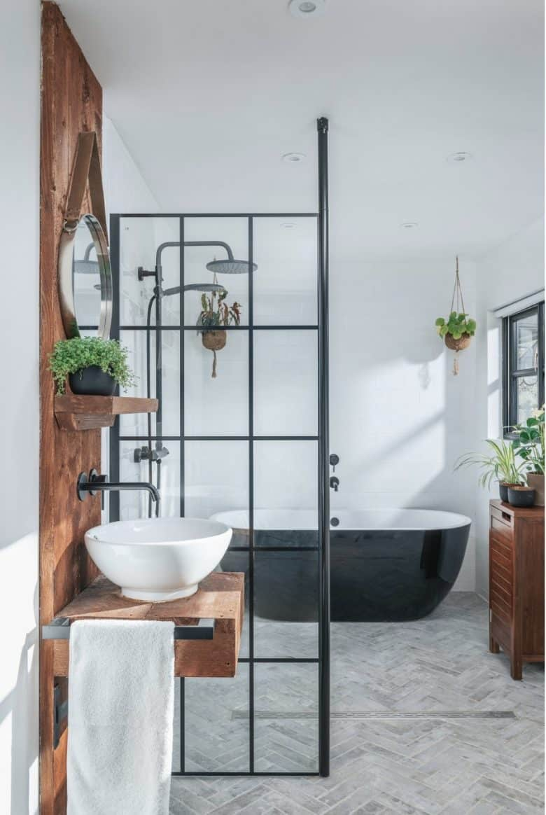 modern rustic bathroom interior with white walls, herringbone tile floor wet room with reclaimed wood splasback panel and white wash bowl with black frame shower panel black taps and shower