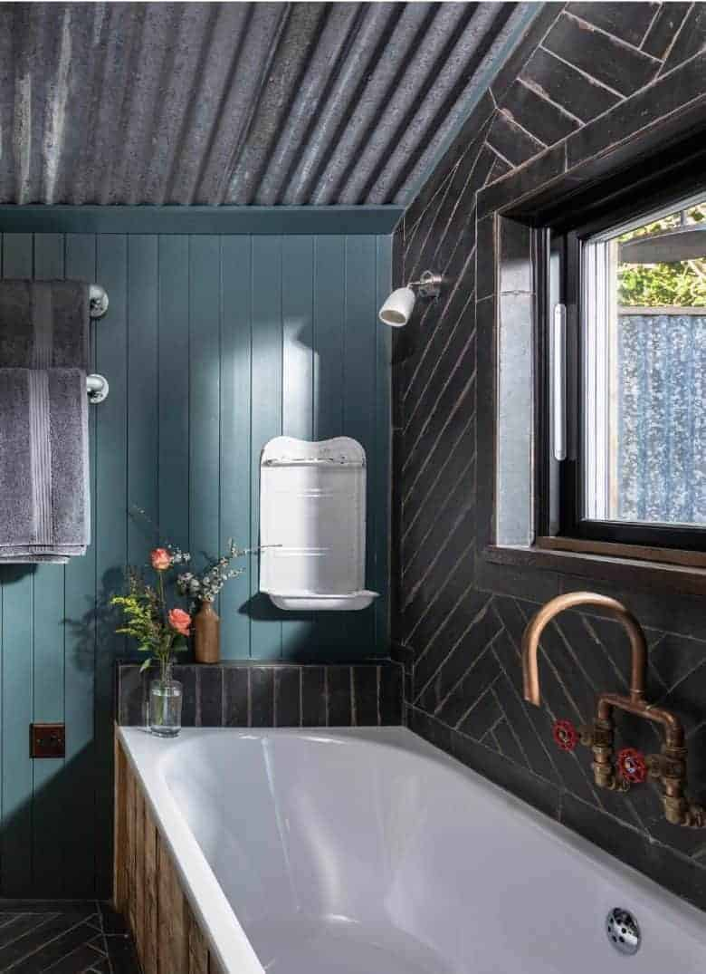 modern rustic bathroom decorating idea combining dark teal tongue and groove wall panelling with reclaimed brass industrial taps, vintage enamel soap holder corrugated metal roof and reclaimed wood panelling on the bath #modern #rustic #bathroom #reclaimed #vintage