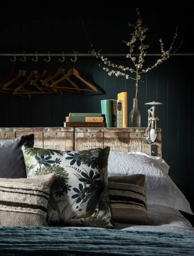modern rustic bedroom decoration idea using reclaimed wood as a bedhead, industrial lighting, dark vintage fabrics, teal velvet, textural knitted cushions and crisp white linen bedding with dark teal tongue and groove walls #modern #rustic #bedroom #reclaimed #teal