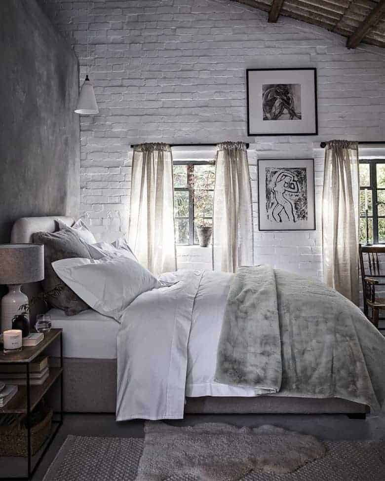 modern rustic bedroom white linen faux fur throw and rustic white painted brick walls and grey concrete with black and white contemporary prints #modern #rustic #bedroom #white #fauxfur