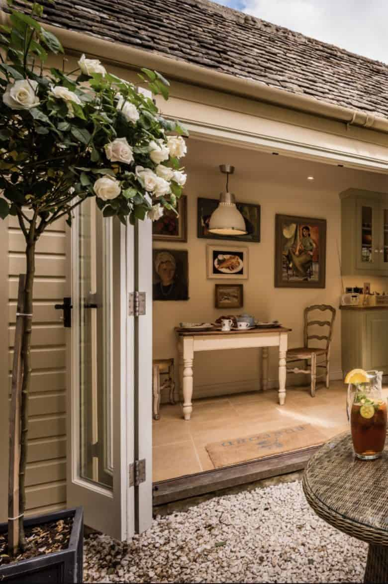love this modern rustic courtyard terrace garden created using simple bifold french doors with stone floor, gravel, original btc lighting and vintage paintings with painted clapboard walls on the exterior it's just one of the beautiful properties available to book through Unique Stays