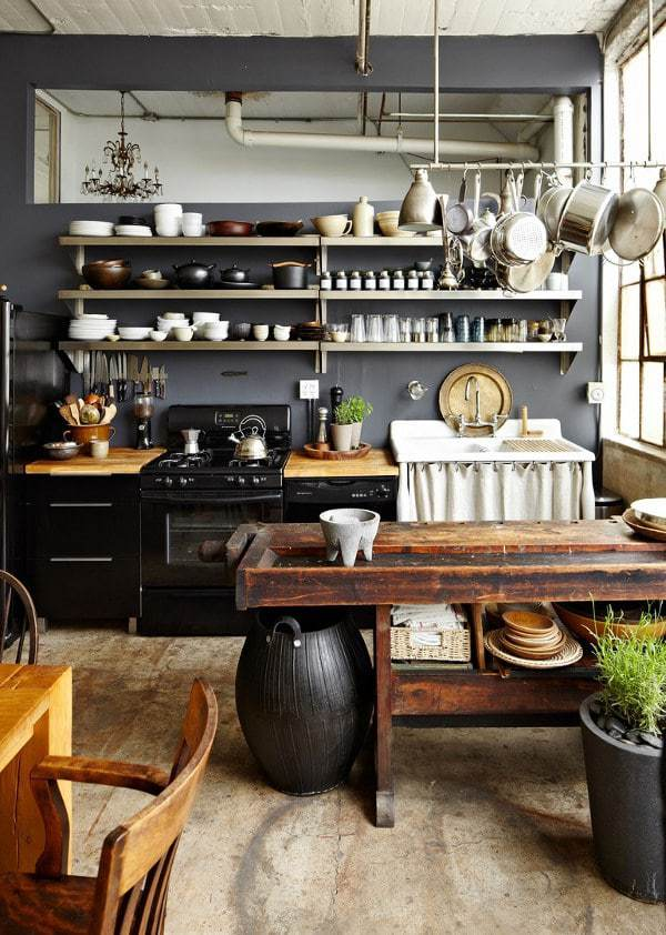 love this modern rustic country kitchen with dark grey walls, open shelves, old farmhouse table and simple rustic ceramics, old wooden chopping boards and simple glass storage jars. click through for more rustic interiors ideas you'll love