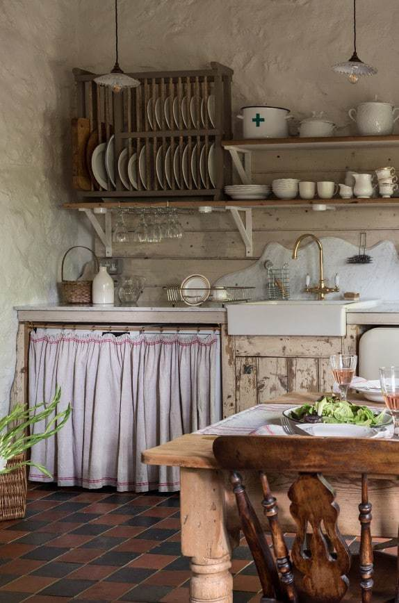 how cute is this rustic country farmhouse kitchen with open shelves, terracotta tile floor, linen cupboard curtain, wooden plate rack, farmhouse table and reclaimed wooden units? Click through for more modern rustic farmhouse interiors ideas you'll love