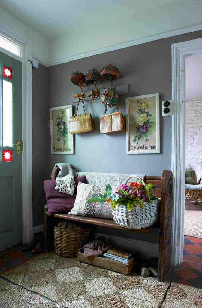 love this quirky rustic country entrance hallway in wales with old wooden church bench, soft blue walls, baskets, vintage prints and vintage finds and hat stand