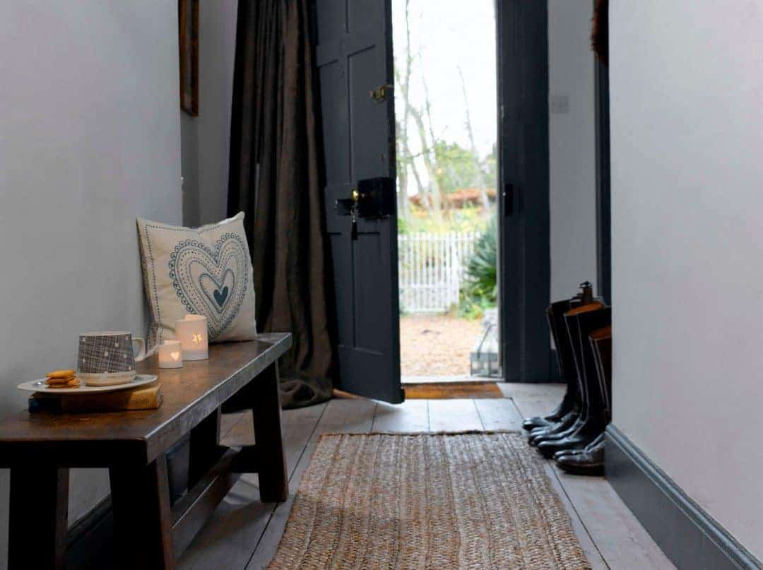love this modern rustic hallway with dark grey farrow and ball door, stripped floor boards and rustic wood bench. Click through for more modern rustic country home ideas you'll love