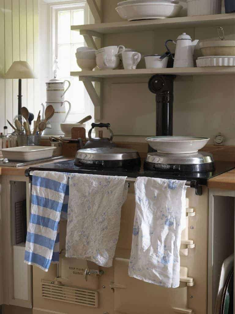 love this modern rustic kitchen with aga and simple country linens, ceramics, wooden spoons and old country range kettle