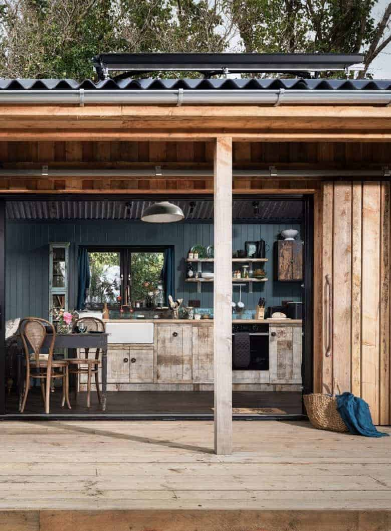 modern rustic kitchen terrace deck with dark teal walls, reclaimed wood industrial lighting, corrugated roof, bifold french sliding doors and vintage table and chairs with open shelving and vintage finds #modern #rustic #kitchen #diner #reclaimed #terrace #deck #teal
